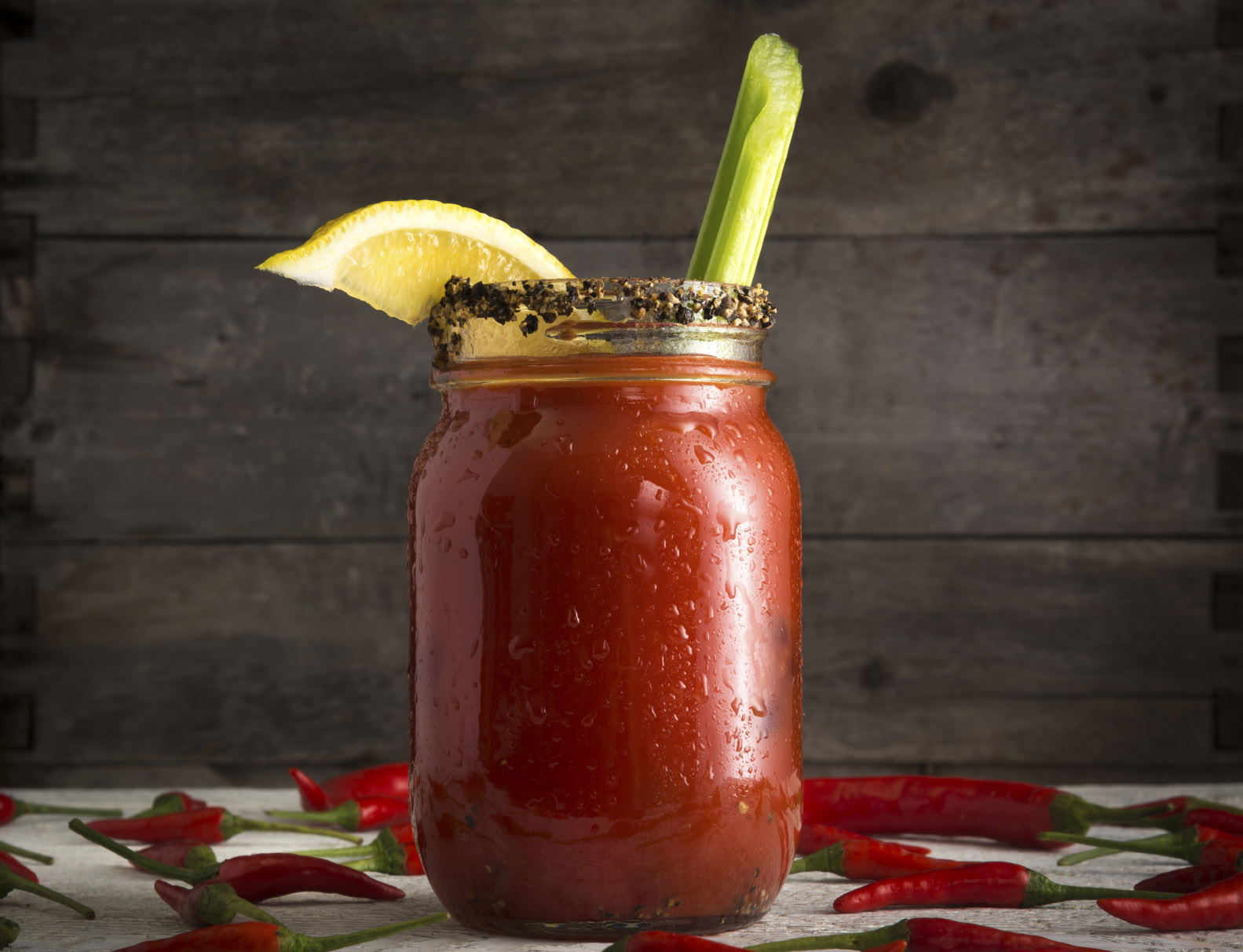Bloody Mary or Bloody Ceasar with celery in mason jar rimmed with black pepper